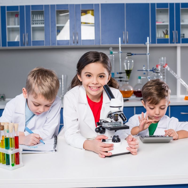 three-kids-in-chemical-laboratory-making-notes-and-using-microscope-and-calculator.jpg